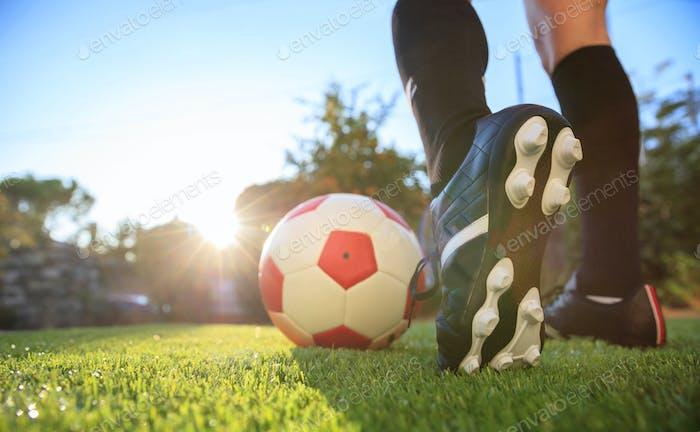 Mujer y un balón de fútbol en la hierba