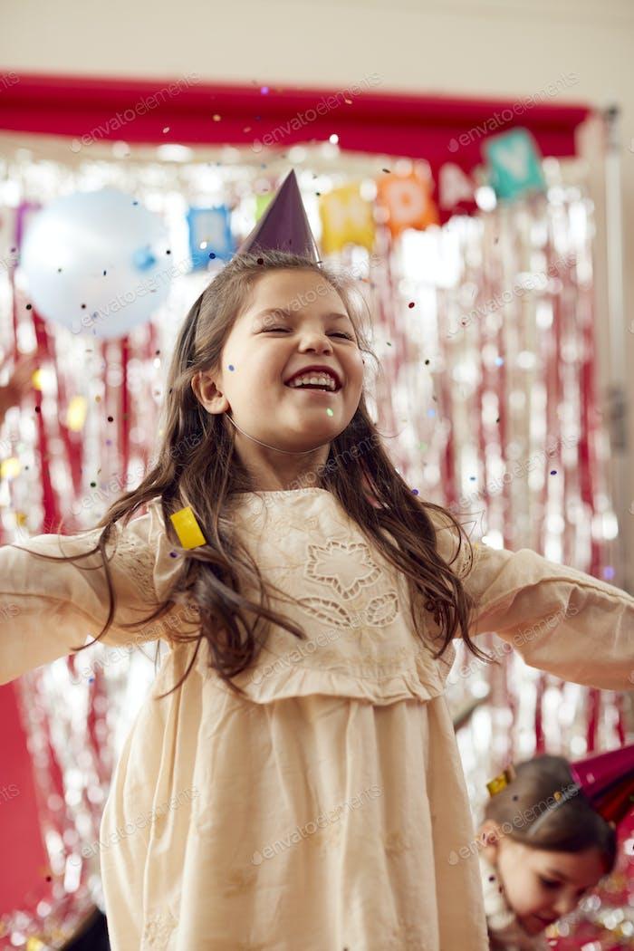 Mädchen mit Partyhut feiert auf Geburtstagsfeier mit Glitzer und goldenem Konfetti