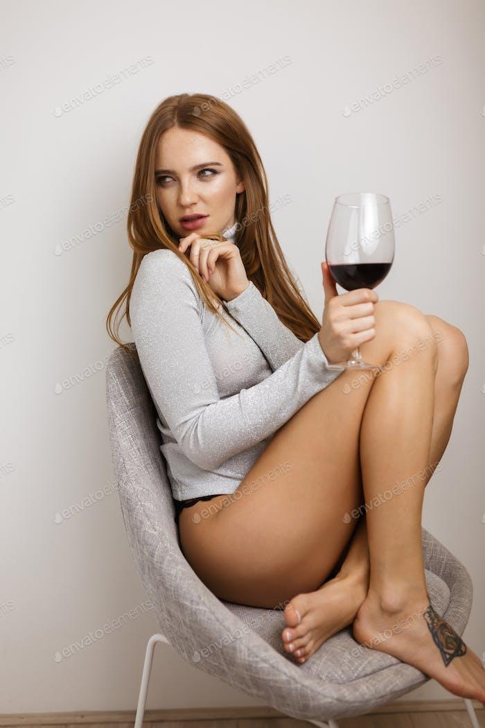 Schöne Dame sitzt im Stuhl mit Glas Rotwein in der Hand geheimnisvoll beiseite schauen