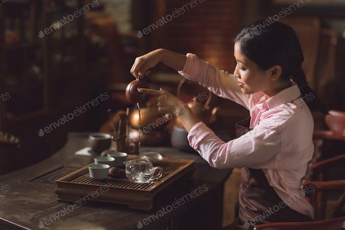 Junge Frau gießt Tee im Zimmer