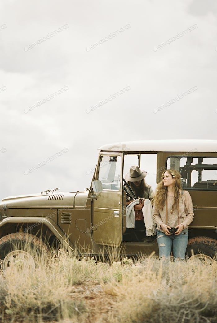 Two women by a 4x4 in a desert, taking a break from the road.