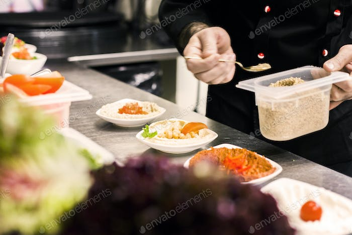 Midsection of chef preparing meze at counter in restaurant kitchen