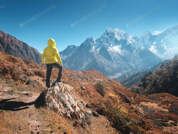 Sporty man on the stone is looking on snow covered mountains