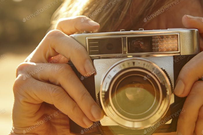 Woman taking pictures with vintage camera. Back light. Travel background.