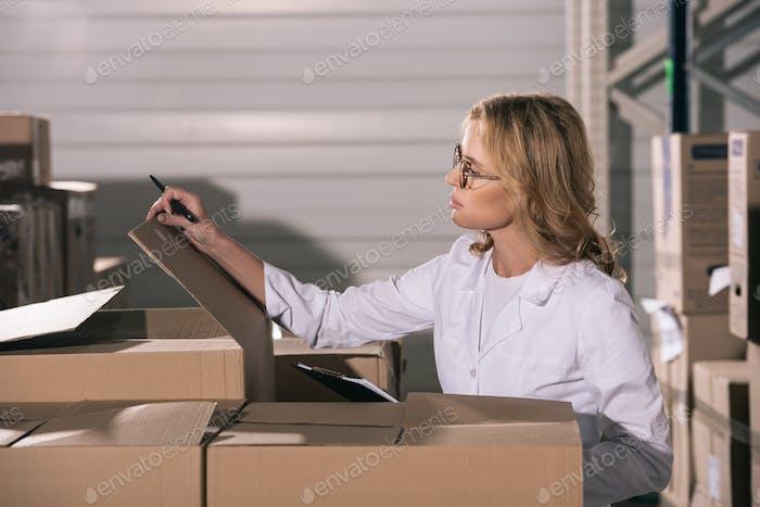focused storekeeper in white coat inspecting cardboard boxes in warehouse