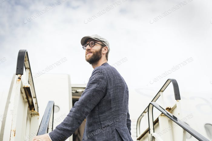 Side view of businessman standing on boarding stairs against sky