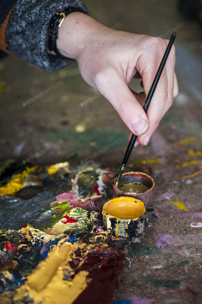 High angle close up of human hand dipping paintbrush into small pot of yellow oil paint.