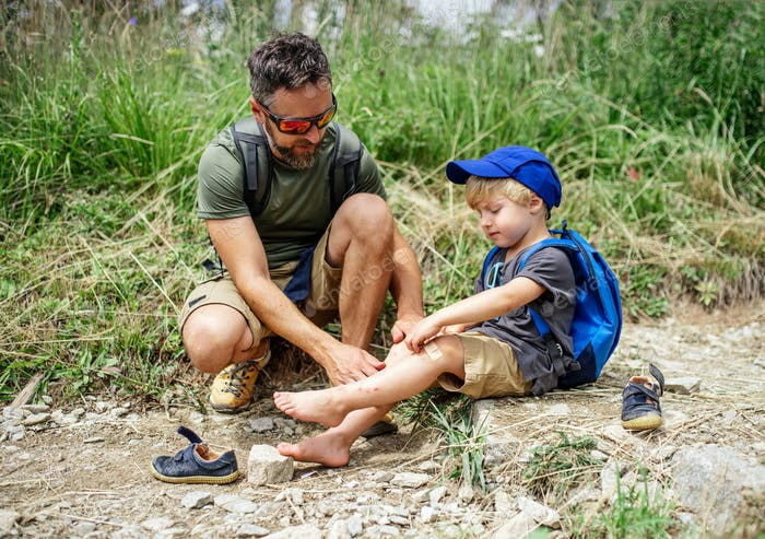 Father with small son hiking outdoors in summer nature, putting plaster on knee