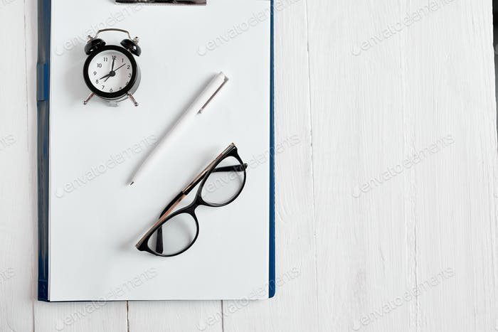 Flat lay of Time management concept, office workplace, blank notepad, glasses and alarm clock.