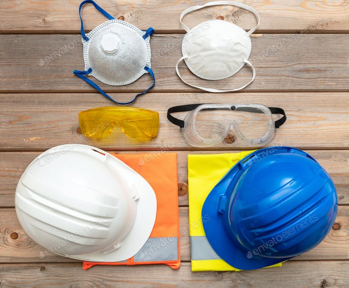 Work safety protection equipment on wooden background.