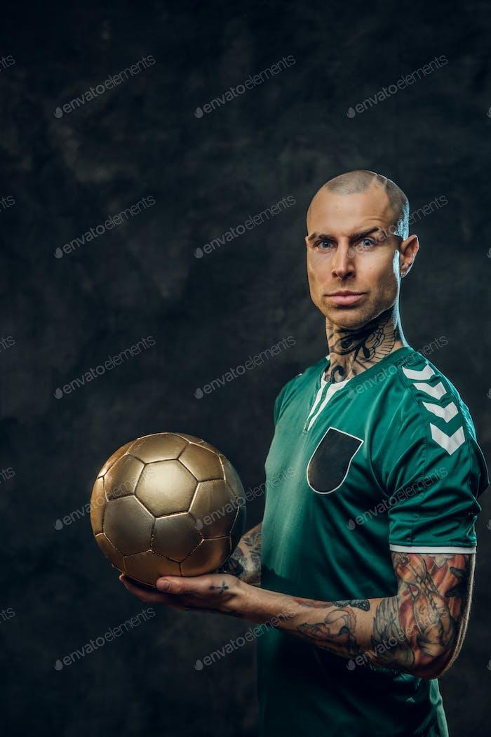 Handsome soccer player holding a golden soccer ball