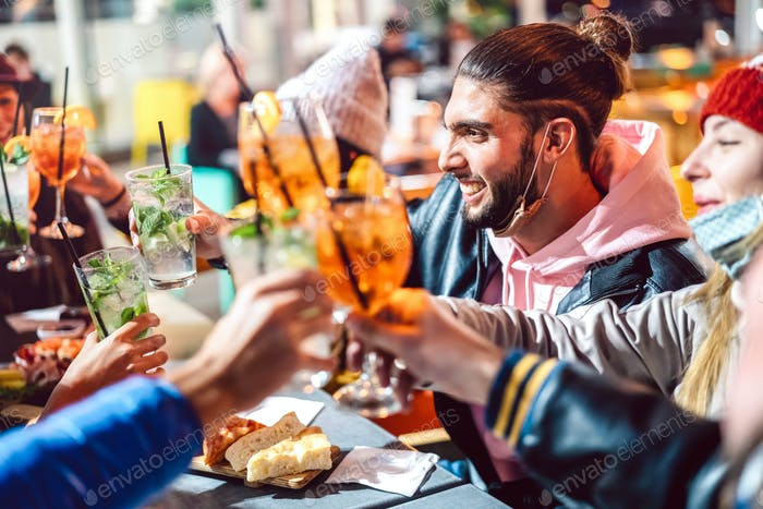 Drunks friends toasting fancy drinks at night bar with open mask