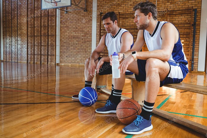Male basketball players talking while sitting on bench