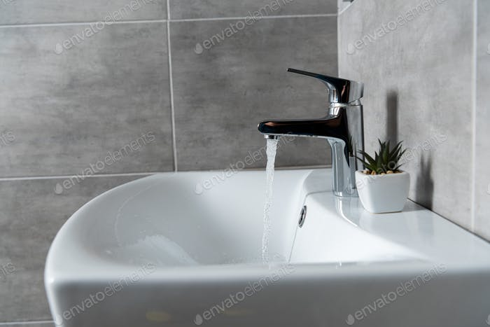 Water flow from sink to ceramic washbasin with plant in modern restroom
