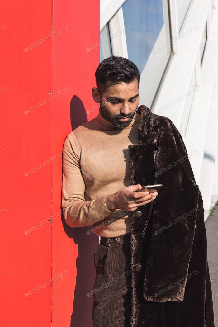 Young Indian man texting in an urban context