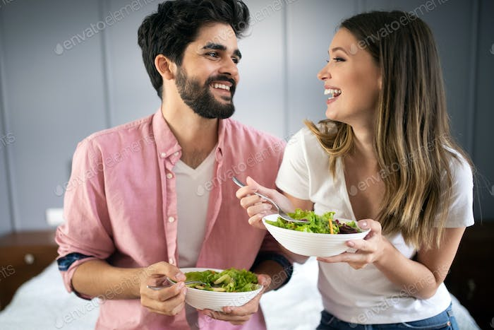 Beautiful young playful couple eating salad together at home