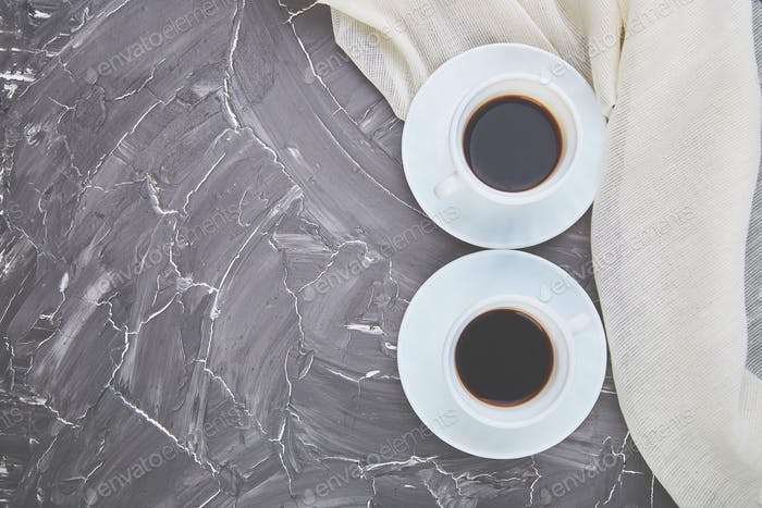 Two white cups of espresso on grey grunge background.