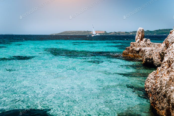 Beautiful turquoise cozy bay surrounded by white cliffs. White yacht afar in the deep blue water