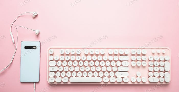 Smartphone and computer keyboard against pink background