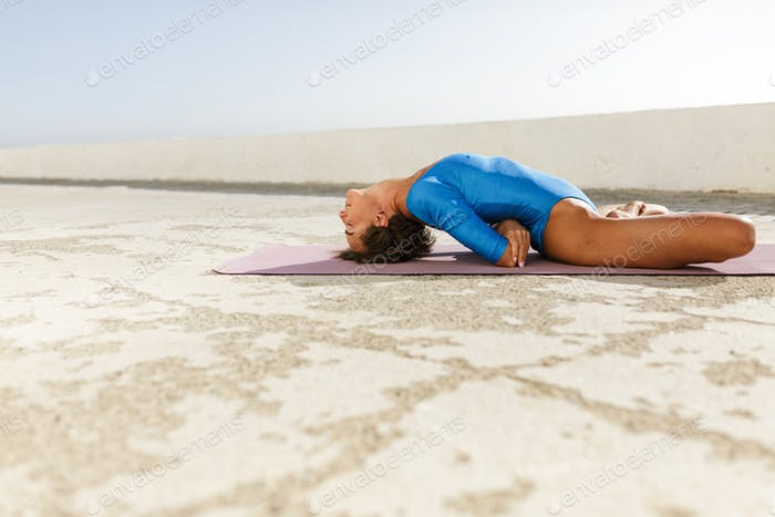 Beautiful lady in blue swimsuit meditating and practicing yoga