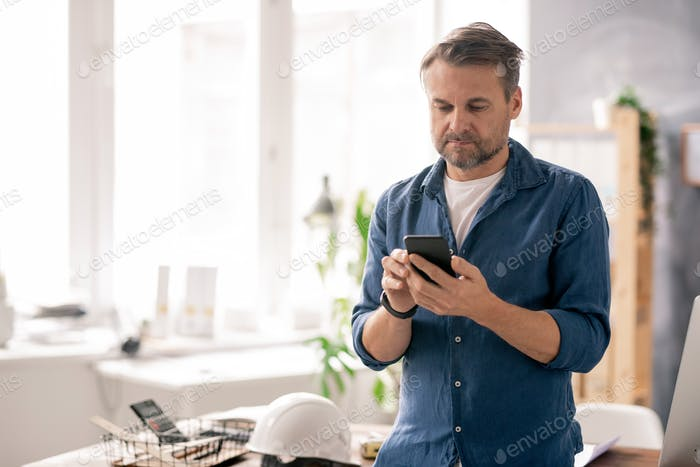 Serious engineer in casualwear scrolling through contacts in his smartphone