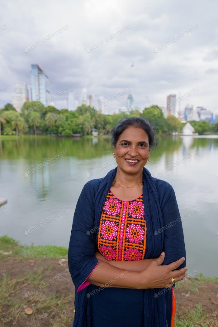 Portrait of mature Indian woman smiling at park