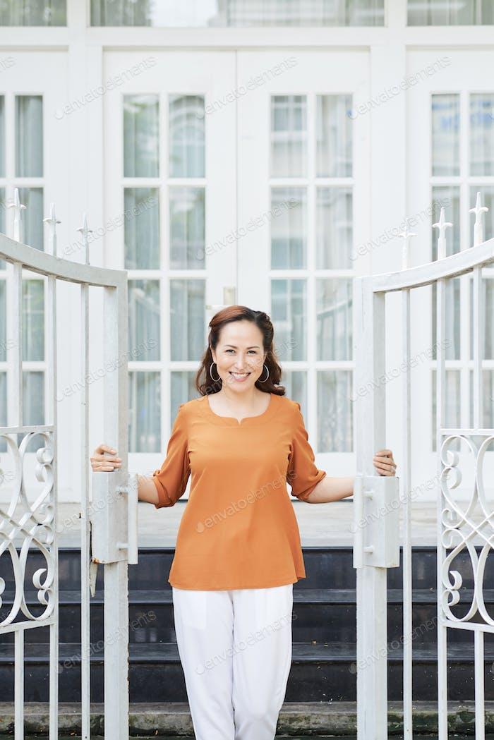 Hausfrau öffnende Tor