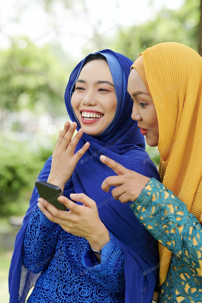 Laughing muslim women with smartphone