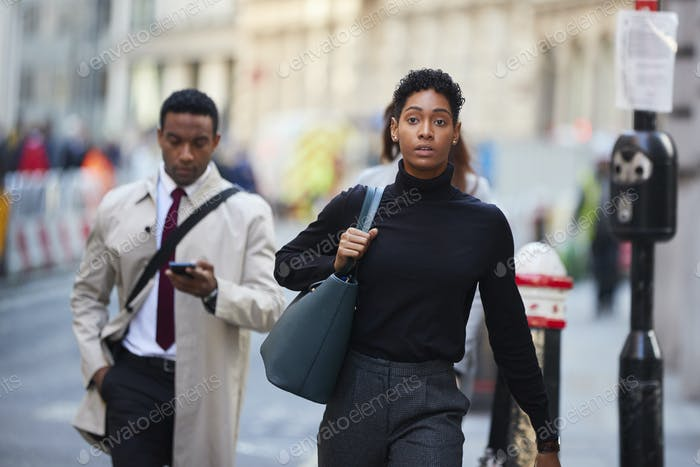 Thumbnail for Young black woman walking in a London street carrying handbag, front view