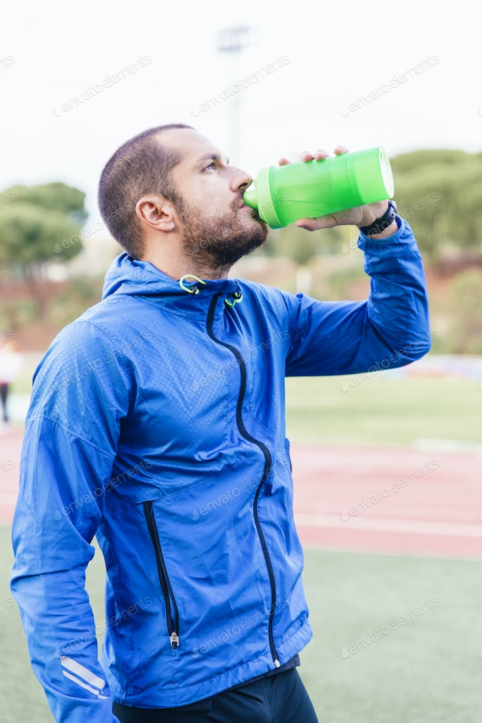 Handsome runner after run resting and drinking water