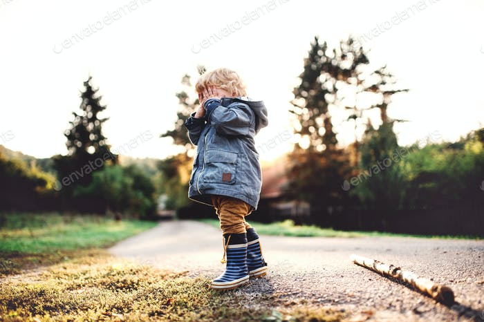 A little toddler boy standing outdoors on a road at sunset, covering his eyes.