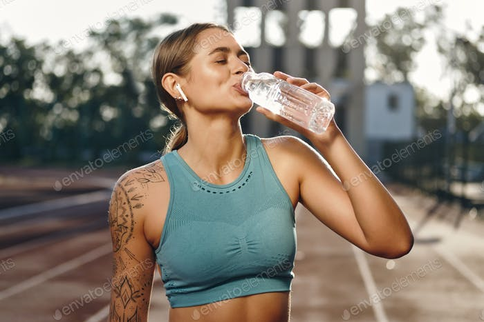 Attractive sporty girl in sportswear happily drinking water after workout on city stadium