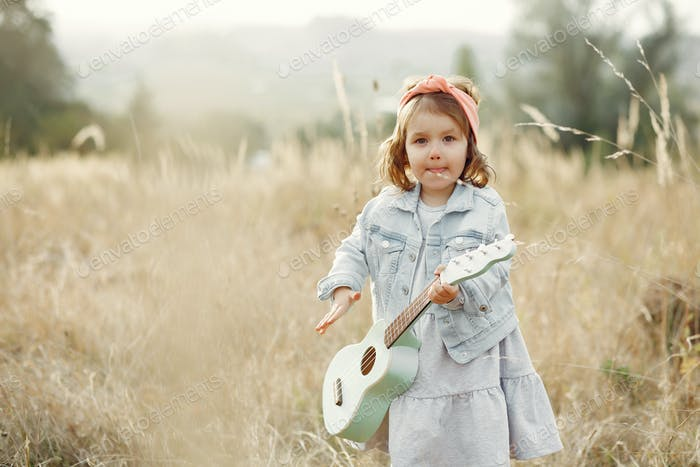 Cite little girl in a autumn park playing on a guitar