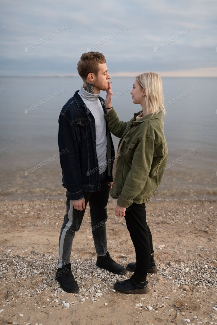 Cool young couple smoking joint on empty coast
