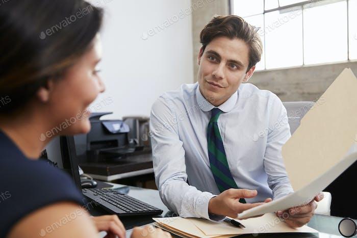 Junge männliche professionelle zeigt Dokumente Frau im Treffen