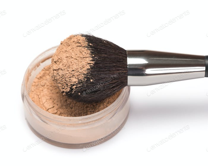 Make-up brush with jar of loose cosmetic powder