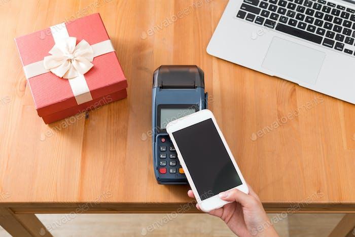 Bezahlen Sie mit Handy auf POS-Maschine für den Kauf Geschenk
