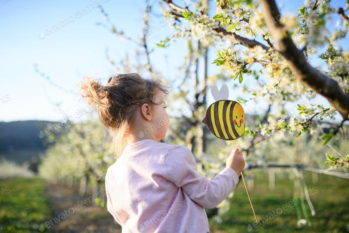 Small toddler girl standing outdoors in orchard in spring, holding paper bee
