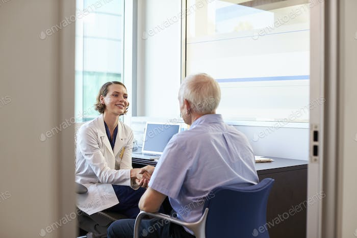 Doctor Shaking Hands With Mature Male Patient In Office
