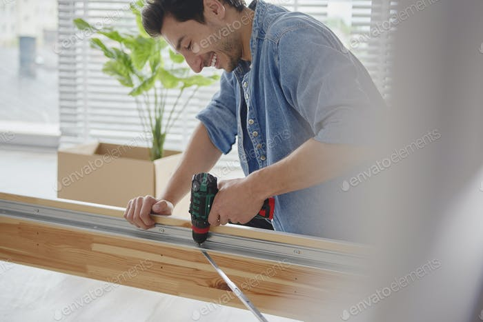 Young man using wireless drill driver to instal furniture