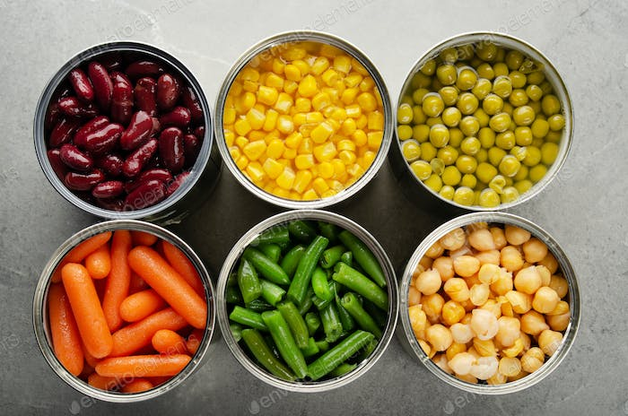 Flat lay view at canned carrots, chickpeas, kidney beans, green beans, peas and corn