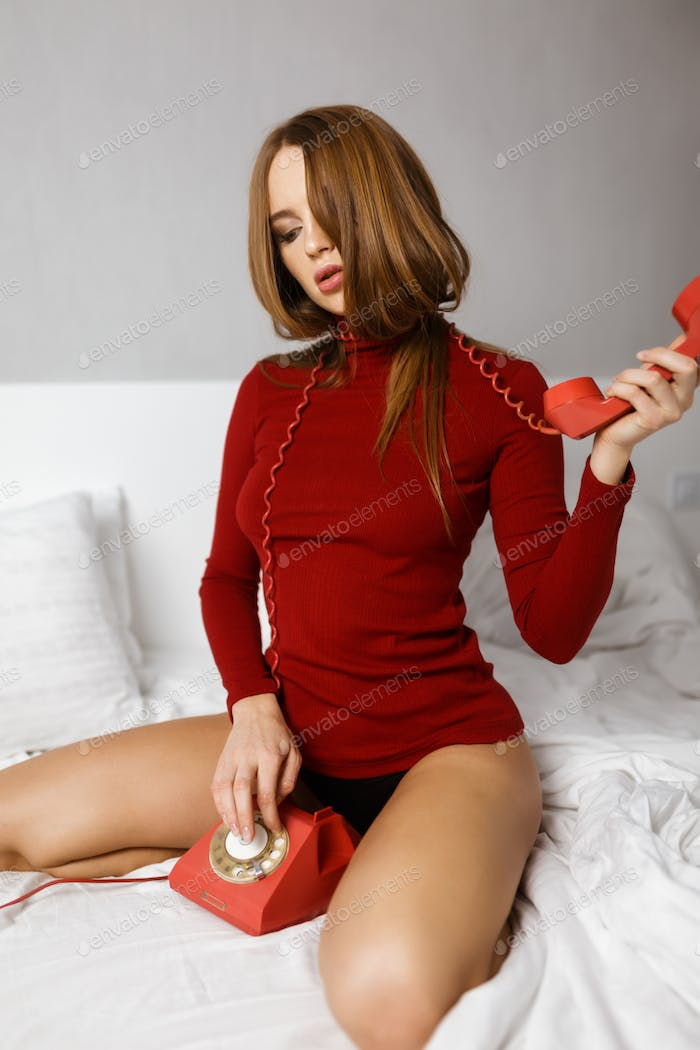 Young thoughtful lady in red turtleneck sitting in bed dialing number on red classic telephone