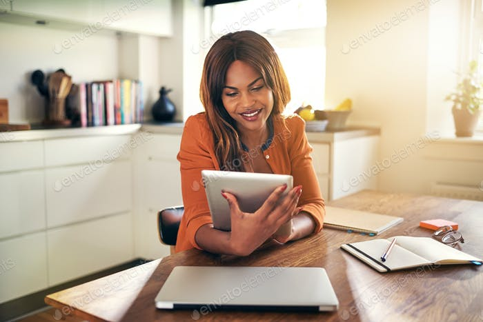 Smiling young woman working from home with a digital tablet