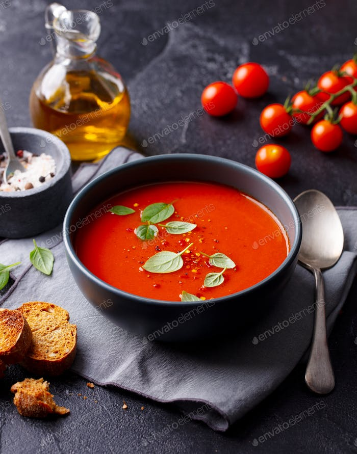Tomato Soup with Basil in a Bowl. Dark Grey Background.