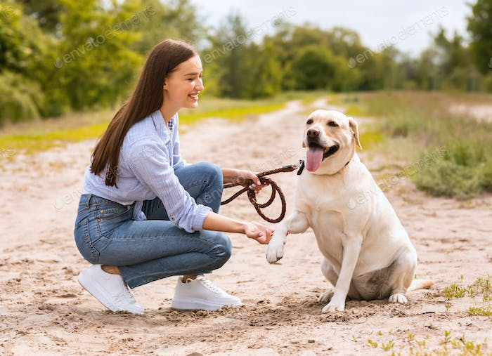 Smiling woman and golden retriever playing outdoors