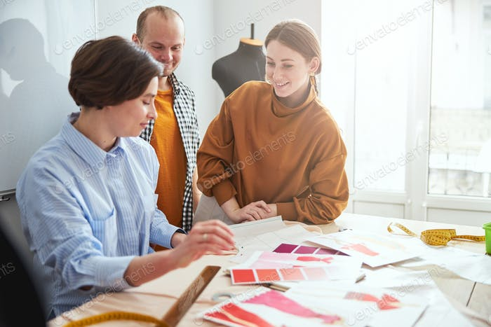 Designers consulting their coworker with about the color