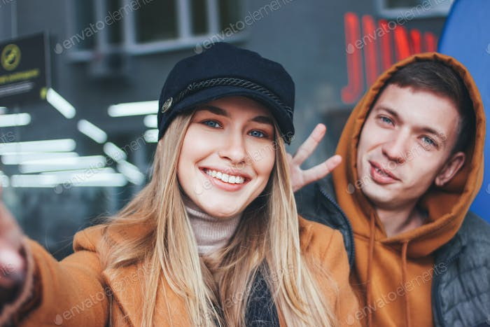 Happy young couple dressed in casual style making selfie on city street in cold season