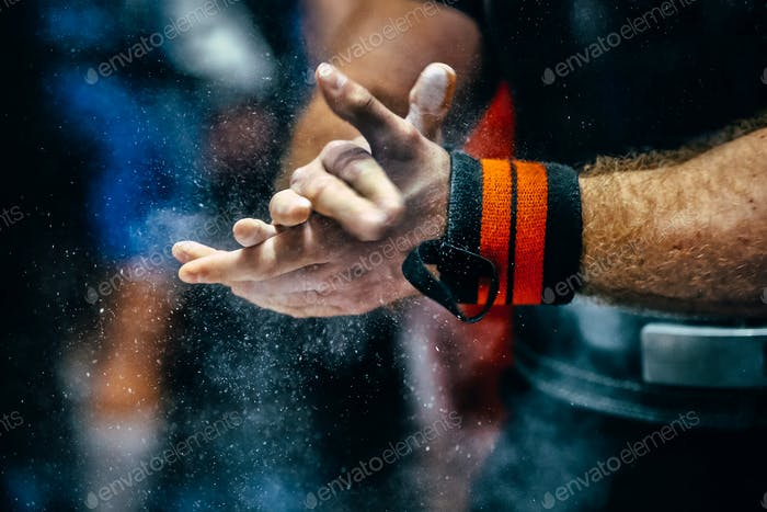 male powerlifter hand in talc and sports wristbands
