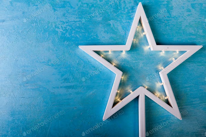 White Christmas star with yellow lights on blue background