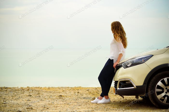 View of young woman traveler looking at sea sunset, sitting on hatchback car with the copy space